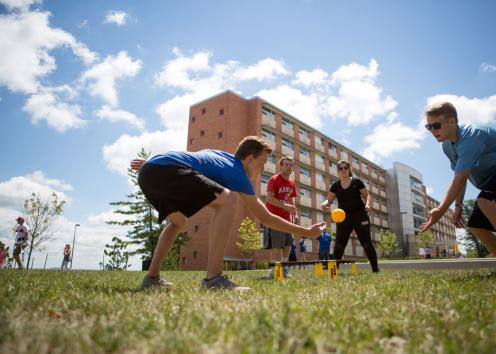Students playing spike ball outside dorms